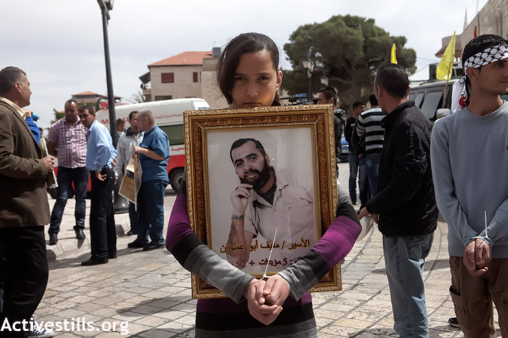 A Palestinian girl who handcuffed herself holds the picture of her jailed uncle during a protest in support of the Palestinian prisoners in the West Bank city of Bethlehem, April 11, 2013. (Photo by: Anne Paq/Activestills.org)