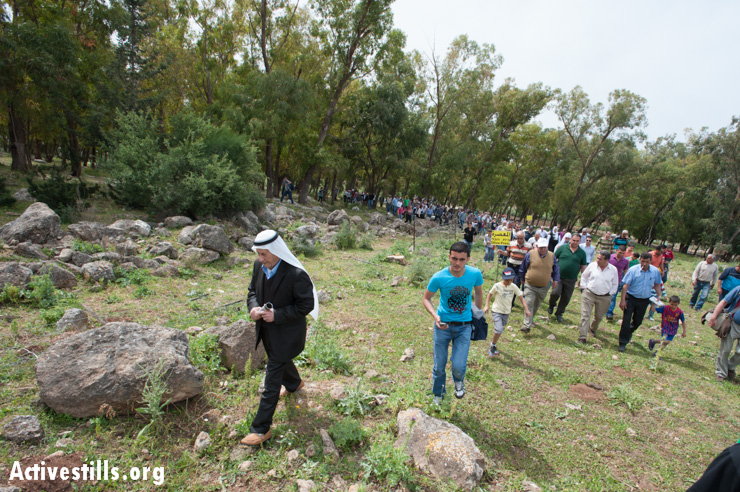 A village elder leads the group as they walk through the remains of Al-Ruways.