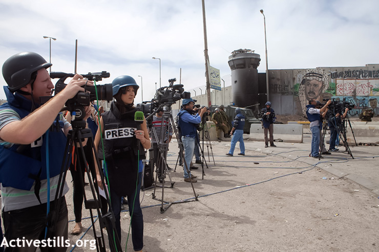 A crowd of journalists stands in front of the Separation Wall during a protest for Land Day, held in front of the Qalandiya checkpoint, West Bank, March 30, 2013. Land Day commemorates the death of six Palestinian protesters at the hands of Israeli forces during mass demonstrations in 1976 against plans to confiscate Palestinian land in northern Israel. (Photo by: Anne Paq/Activestills.org)