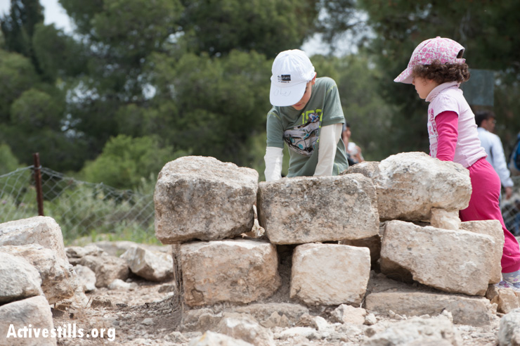 Children explore the cemetery of Al-Ruways, one of the few remaining visible traces of the village.