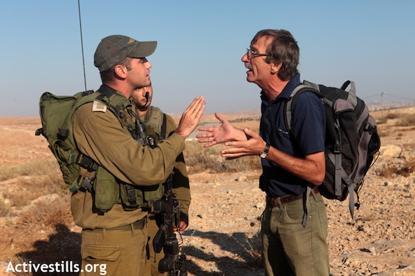 A Ta'ayush activist argues with an Israeli soldier in the South Hebron hills, August 11, 2012. (Photo: Anne Paq/Activestills.org)