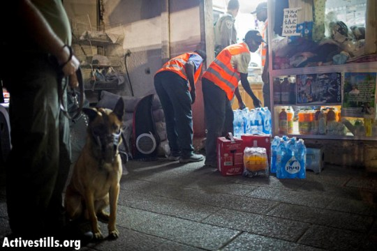Policeman and an attack dog watch over African workers emptying a store belonging to asylum seekers. (Oren Ziv/Activestills.org)