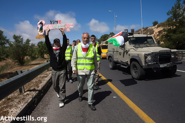 Palestinian activists march on Road 60, the main north-south route through the West Bank, in a Nakba Day protest, May 15, 2013. (Photo by: Anne Paq/Activestills.org)