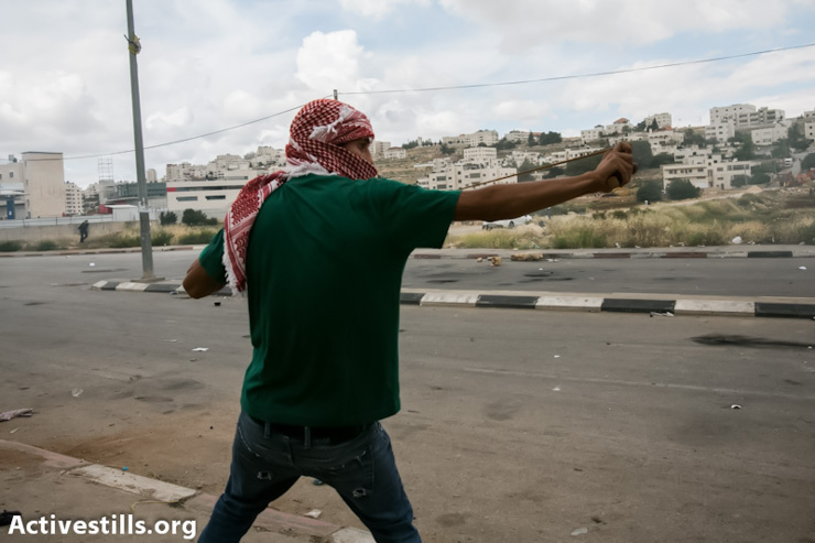 A Palestinian youth uses a slingshot during clashes with the Israeli army during a protest to commemorate the Nakba, outside the Ofer military prison, West Bank, May 15, 2013. (Photo by:Yotam Ronen/Activestills.org)