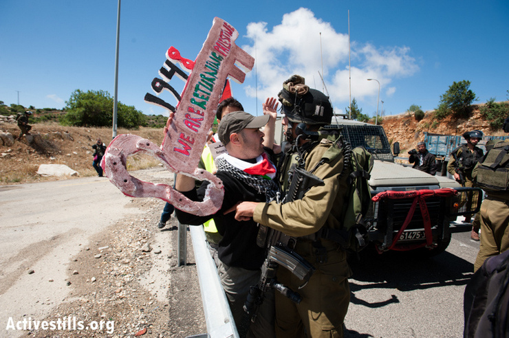 "Palestinian activists confront Israeli soldiers during a march on Road 60, the main north-south route through the West Bank, in a Nakba Day protest, May 15, 2013. The Nakba, literally, the ""catastrophe,"" marks the massive deportation of more then 700,000 Palestinian, made refugees and driven out of what became the State of Israel in 1948. (Photo by: Ryan Rodrick Beiler/Activestills.org)"