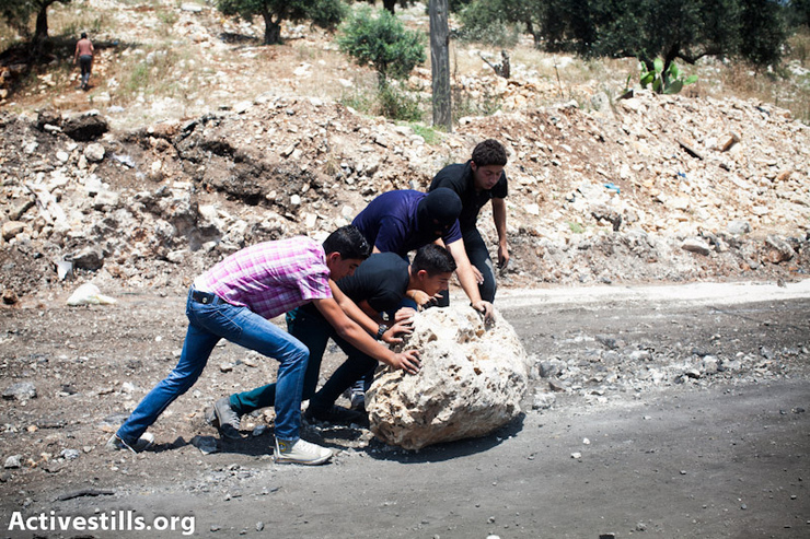 Protesters push a rock in an attempt to block the road during the weekly demonstration in Kfer Qaddum, a West Bank village located east of Qalqiliya, May 10, 2013. There have been regular demonstrations in Kfer Qaddum since July, 2011, protesting the blocking of the main road east of the village, which used to link it to Nablus. (Photo by: Yotam Ronen/Activestills.org)