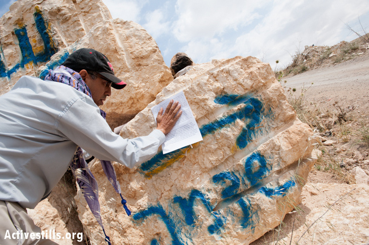 A Palestinian activist posts a bulletin protesting the attempt to create a new Israeli settlement called Shdema, on land belonging to the West Bank town of Beit Sahour, May 12, 2013. All Israeli settlements on occupied Palestinian territory are illegal under international law. (Photo by: Ryan Rodrick Beiler/Activestills.org)