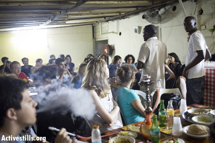 "A Sudanese asylum seeker speaks to local activists during a solidarity dinner event at his restaurant following a raid by the Israeli authorities the previous night, south Tel Aviv, May 13, 2013. Local activists organized a solidarity dinner event, in an attempt to recoup some of the loses the restaurant suffered after municipal inspectors raided the place, pouring bleach into pots of food destroying Several hundred kilos of food, allegedly because the establishment is ""a danger to public health."" (Photo by: Oren Ziv/Activiestlls.org)"