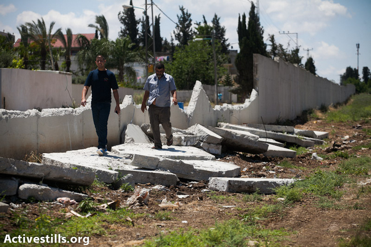 A section of a separation wall, built between the Pardes Shanir Arab neighborhood in Lod and the Jewish moshav (a cooperative settlement) of Nir Tzvti, was destroyed a few day ago by unknown persons, Lod, May 12, 2013. The wall, 1.5 km long and 4 meters high, was built in 2003, creating a symbolic and territorial partition between the Arab and Jewish residents. Since about 50 meters of the wall were destroyed, police forces raided the Arab neighborhood, arresting a few residents. (Photo by: Yotam Ronen/ Activestills.org)