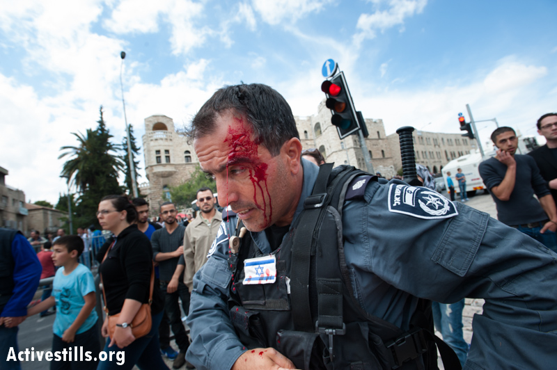 """An Israeli policeman bleeds from an injury sustained attempting to eject Palestinians commemorating Nakba Day at Damascus Gate, East Jerusalem, May 15, 2013. According to Haaretz, """"In Jerusalem, two policemen were lightly injured when Palestinian protesters threw stones. Two ultra-Orthodox men were lightly injured when they were beaten by Palestinians.""""(Photo by: Ryan Rodrick Beiler/Activestills.org)"""