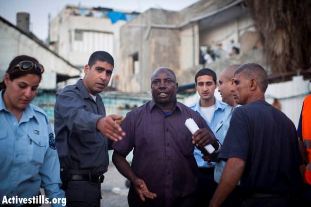 Tel Aviv municipality officials showing an asylum seeker out of his resturant (Oren Ziv / Activestills)