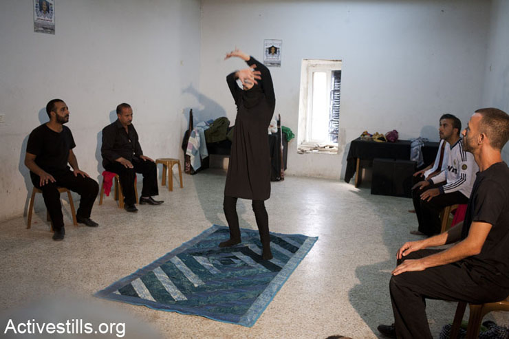 """Members of """"The Freedom Theatre"""" perform a scene about the spring that was confiscated by the settlers of the nearby illegal settlement of """"Halamish."""" In December 2009, the residents of Nabi Saleh and the neighboring village of Dier Nidham started demonstrations against confiscations of their land by the Israeli army and settlers. The protests have continued to take place every week since then."""