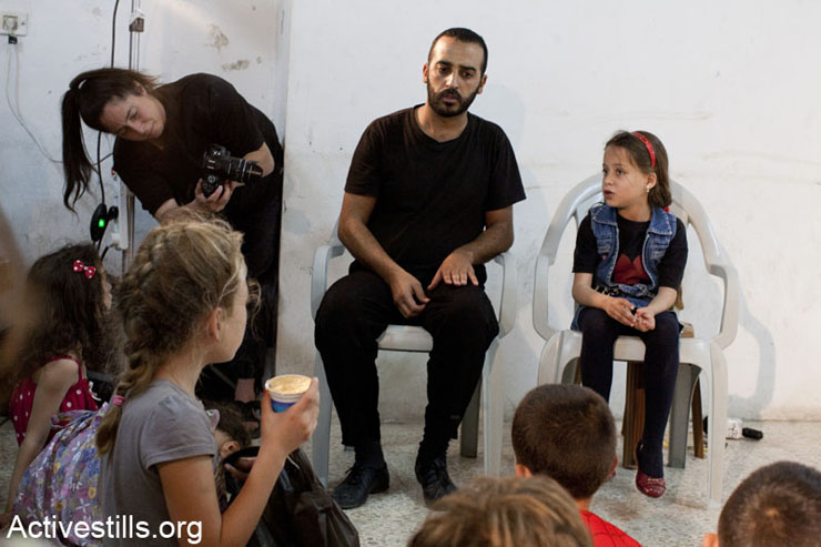"""Members of """"The Freedom Theater"""" improvising a scene with a Palestinian girl telling her story during a play."""