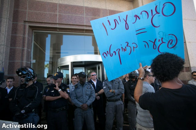 """Closing a paper = a damage to democracy"". Journalist facing guards at the offices of one of Ma'ariv's owners (Yotam Ronen / Activestills)"