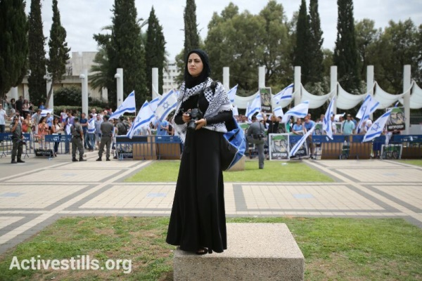 A Palestinian photographer stands during a minute of silence commemorating the Nakba at a ceremony held by Palestinian and Israeli students at the entrance to Tel Aviv University. Right-wing activists protesting the ceremony and policemen are seen in the background. May 13, 2013 (photo: Yotam Ronen / Activestills)
