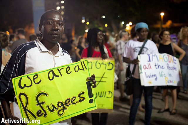 """An African refugee holds a sign reading: """"We are all refugees"""", during a demonstration in Tel Aviv against racism and the government's policy against African refugees, July 28, 2012. (photo: Activestills)"""
