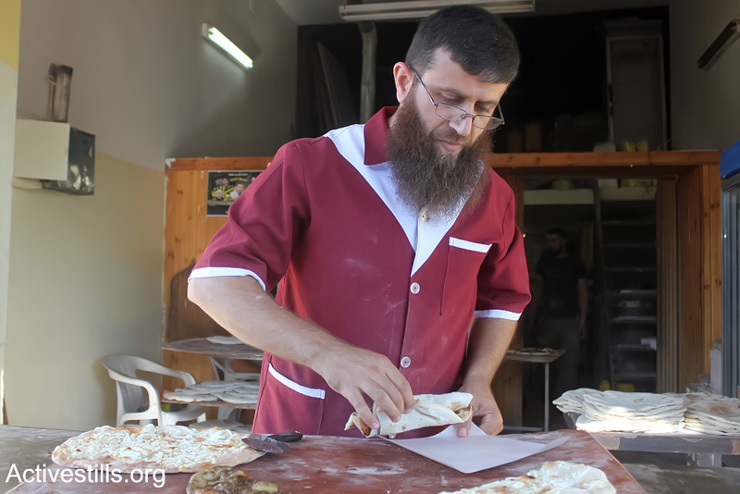 The Palestinian former prisoner Khader Adnan working at his bakery in the West Bank Village of Qabatiya near Jenin, June 21, 2013. Adnan was released in 2012 after a hunger strike but re-arrested in 2014. (Photo by: Ahmad Al-Bazz/ Activestills.org)