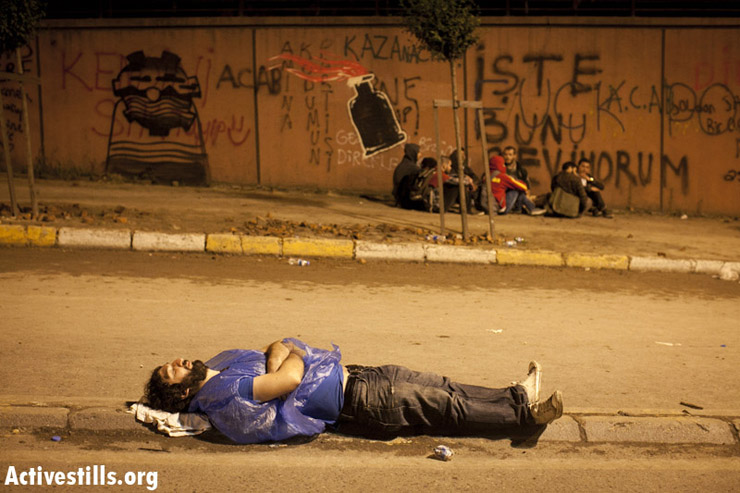 A protester sleeps in a street near Taksim Square in central Istanbul in the early morning hours of June 3, 2013. Police fired tear gas at activists after they set up barricades around the square and tried to march toward the direction of the local soccer stadium.Oren Ziv/ Activestills.org