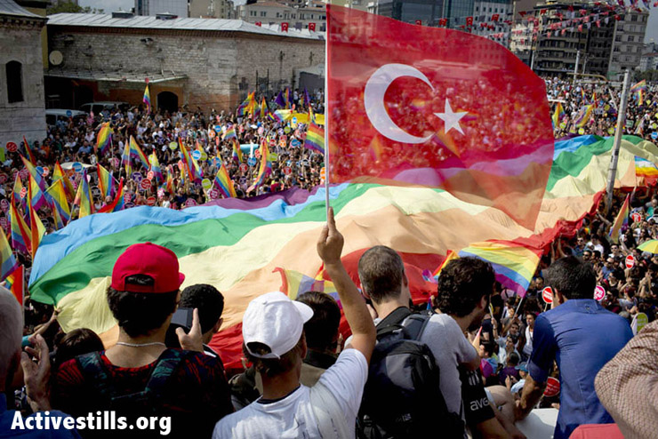A man waves the Turkish flag as people gather in Taksim Square, at the beginning of the annual pride parade, Istanbul. Photo by: Oren Ziv/Activestills.org