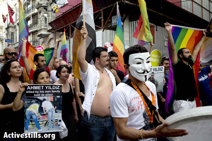 A woman holding a poster with Ahmet Yildiz's picture, during the Pride Parade. Yildiz was shot leaving a cafe near the Bosphorus. Photo by: Oren Ziv/Activestills.org