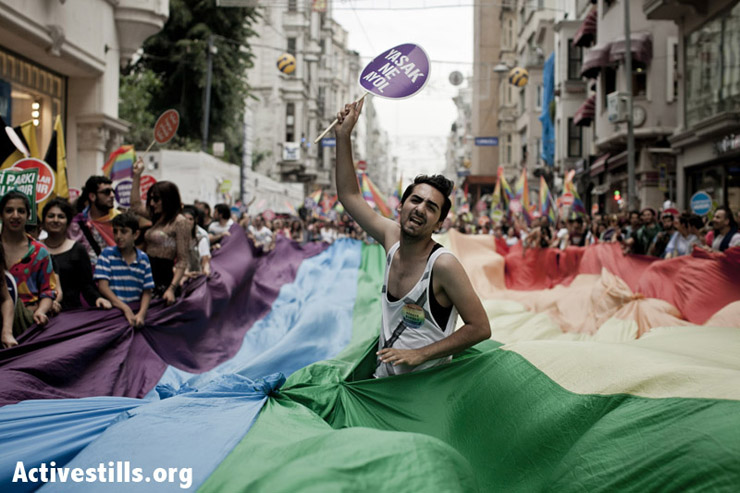 A protester shouting slogans while marching inside the pride flag. Photo by: Shiraz Grinbaum/Activestills.org