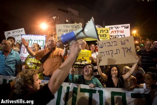 Demonstrators holding anti-Capitalist and anti-occupation signs (Oren Ziv / Activestills)