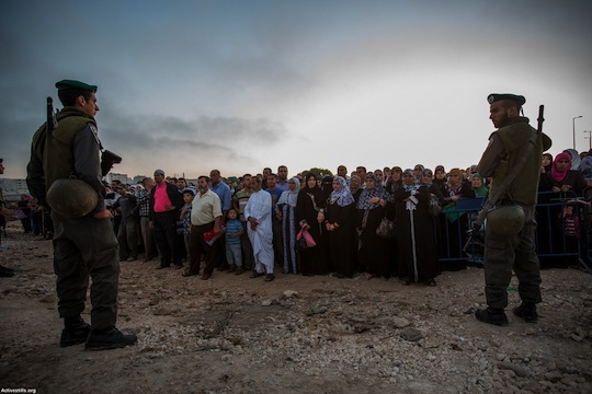Border Police officers stand in front of Palestinian as they wait to cross from the Qalandiya checkpoint outside Ramallah, West Bank, into Jerusalem to attend the Ramadan Friday Prayers in Al-Aqsa Mosque, July 26, 2013. (Photo: Activestills.org)