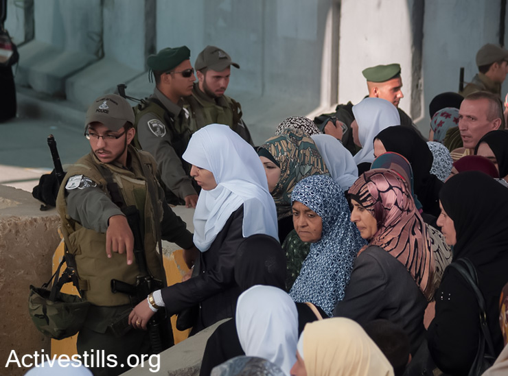 Palestinian women wait to cross from Qalandiya checkpoint outside Ramallah, West Bank, into Jerusalem to attend the second Ramadan Friday prayers in the Al-Aqsa Mosque, July 19, 2013. (Photo by guest photographer: Nidal Elwan/ Activestills.org)