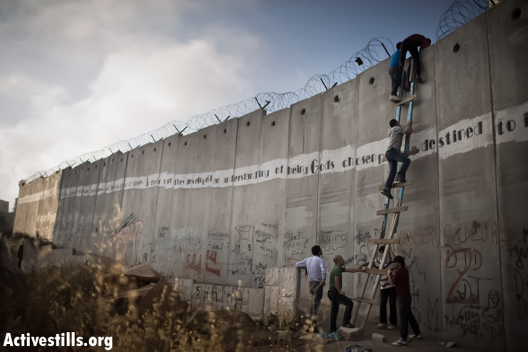 Palestinians use a ladder to climb over the Israeli wall in A-Ram, north of Jerusalem, on their way to Al-Aqsa Mosque, in the Old city of Jerusalem to attend the second Friday prayer of Ramadan, July 19, 2013. (Photo by: Oren Ziv/ Activestills.org)