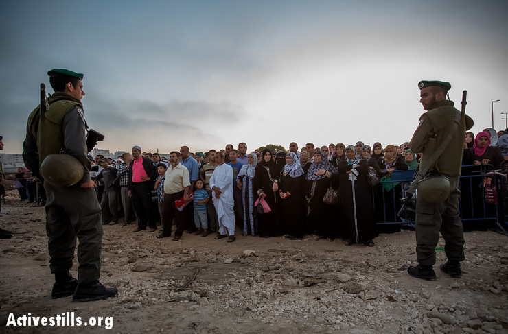 Border police officers stand in front of Palestinians as they wait to cross from the Qalandiya checkpoint outside Ramallah, West Bank, into Jerusalem, July 26, 2013. (Photo: Activestills.org)