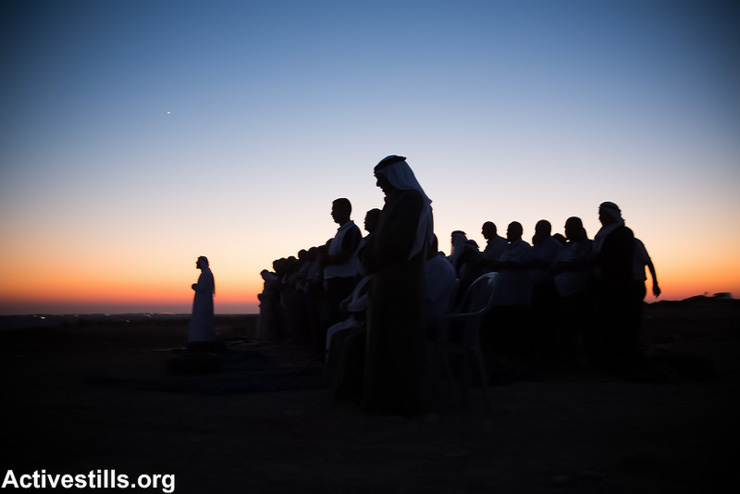 People pray after the Iftar meal – the breaking of the Ramadan fast – at Al Araqib village during an event to marking three years to the first demolition of the village, July 27, 2013. Al Araqib has been demolished 54 times. (Photo by: Yotam Ronen/Activestills.org)