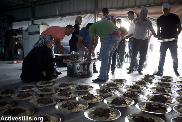 Residents of the unrecognized Bedouin village of Al Araqib prepare food for the Iftar meal to break the fast during the month of Ramadan, as Bedouins and activists gather to mark three years since the first demolition of the village, July 27, 2013. The unrecognized village of Al Araqib has been demolished 54 times by the Israeli authorities since 2010. (Photo by: Oren Ziv/Activestills.org)