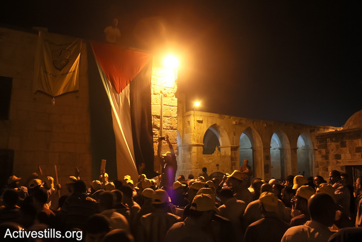 Activists raise the Palestinian flag over Al-Aqsa Mosque in East Jerusalem during the night prayer of Ramadan, August 04, 2013. (Photo by: Ahmad Al-Bazz/Activestills.org)