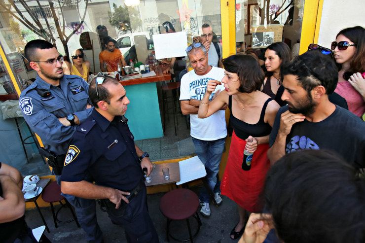 Police try to close down the Albi coffee shop, while activists are standing ground, August 27, 2013. (photo: Yotam Ronen/Activestills.org)