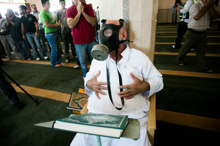 An old man wears a gas mask inside the village mosque after Israeli army shot tear gas during Friday noon prayers on August 23, 2013 in Kfer Qaddum, a West Bank village located east of Qalqiliya. (photo: Yotam Ronen/Activestills.org)