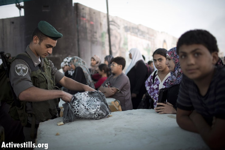 A Israeli border policeman check the bag of a Palestinian woman as she wait to cross from Qalandiya checkpoint outside Ramallah, West Bank, into Jerusalem to attend the Ramadan Friday Prayer in the Al-Aqsa Mosque, July 26, 2013. (Photo by: Oren Ziv/Activestills.org)