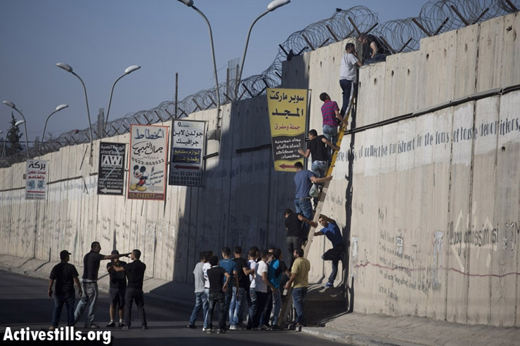 Palestinians use a ladder to climb over the Israeli Separation Wall in A-Ram, north of Jerusalem, on their way to Al-Aqsa mosque to attend the third Friday prayer of Ramadan, 26 July 2013. (Photo by: Oren Ziv/Activestills.org)