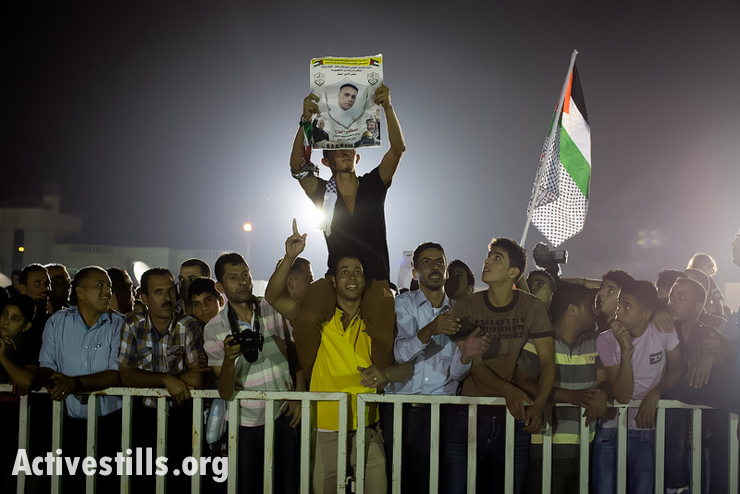 Palestinians celebrate as they wait for the arrival of prisoners freed from Israeli detention in the headquarters of Palestinian President Mahmoud Abbas in the West Bank city of Ramallah, August 14, 2013. 26 Palestinian prisoners will be released, 15 to Gaza and 11 sent to West Bank, as part of Israeli-Palestinian negotiations. (Photo: Activestills.org)
