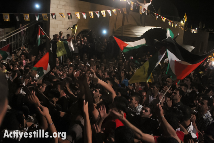 Palestinians celebrate the arrival of Husni Sawallha and Mohammed Sawallha, Palestinian prisoners who spent 23 years in Israel prisons, Izmut village, West Bank, August 14, 2013. Twenty-six Palestinian prisoners from Gaza and West Bank were released as the first stage of a prisoner release, secured by U.S. Secretary of State John Kerry ahead of renewed peace talks. A total of 104 Palestinian prisoners, all jailed before the start of the Oslo peace talks 20 years ago, are eventually supposed to be released over the next nine months. (Photo by: Ahmad Al-Bazz/Activestills.org)