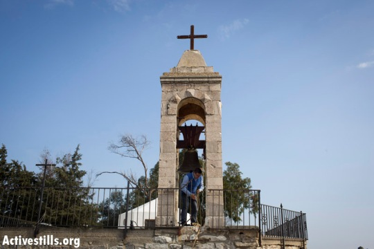 A villager in Bir'em handles the tower bell on the old church (Oren Ziv / Activestills)