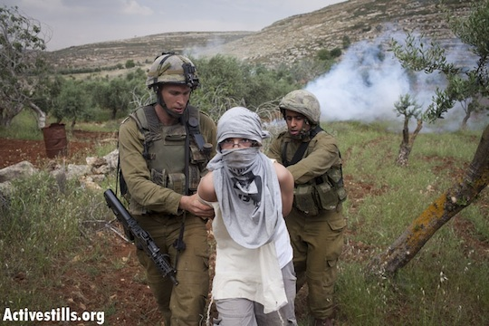Soldiers arrest a masked settler (Photo: Oren Ziv/Activestills.org)