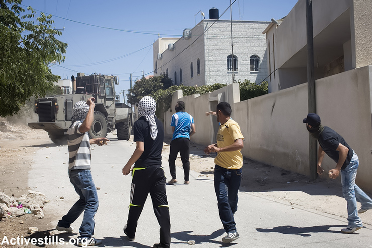 Palestinian youth throw stones towards an Israeli army bulldozer during the weekly demonstration in the West Bank village of Kfer Qaddum, August 9, 2013. There have been regular demonstrations in Kfer Qaddum since July, 2011, protesting the blocking of the main road east of the village which used to link it to Nablus. (Photo: Yotam Ronen/Activestills.org)