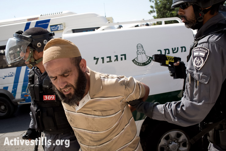 Israeli policemen arrest a Palestinian man after they shot him with a Taser gun in the East Jerusalem neighborhood of Ras al Amud, September 27, 2013. Israeli police prevented Palestinian worshipers under 50 from entering Al-Aqsa Mosque. After the prayers, clashes started in different neighborhoods in East Jerusalem. (photo: Oren Ziv/Activestills.org)