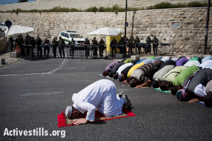 Palestinians pray outside the Lions Gate of Jerusalem's Old City, September 27, 2013. Israeli police prevented Palestinian worshipers under the age of 50 from entering Al-Aqsa Mosque so Palestinians prayed in different locations near the checkpoints. (photo: Oren Ziv/Activestills.org)