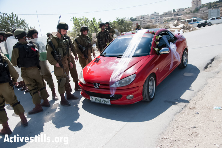 A Palestinian car decorated for a wedding passes by Israeli soldiers blocking the path of the weekly demonstration against the Israeli separation barrier in the West Bank village of Al Ma'sara, September 27, 2013. If built as planned, the wall would cut off the village from its agricultural lands. (photo: Ryan Rodrick Beiler/Activestills.org)