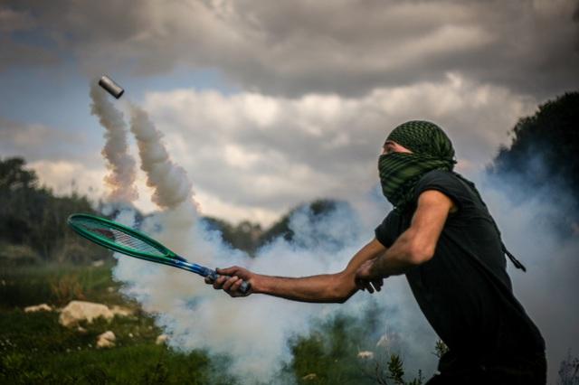 """Return Serve"", a Bil'in demonstrator sending tear gas back to the army (Photo: Hamde Abu Rahma, from the book)"