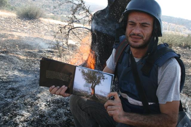 Burning trees, past and present. Abu Rahma and his book at a demonstration (Haggai Matar)