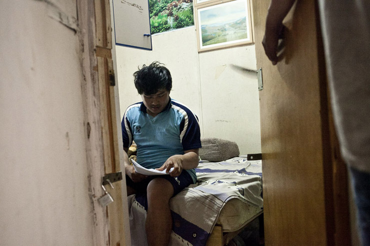 "A worker in his room reading a leaflet distributed by ""Kav Laoved,"" Kfar Varburg, August 31, 2013. (Shiraz Grinbaum/Activestills.org)"