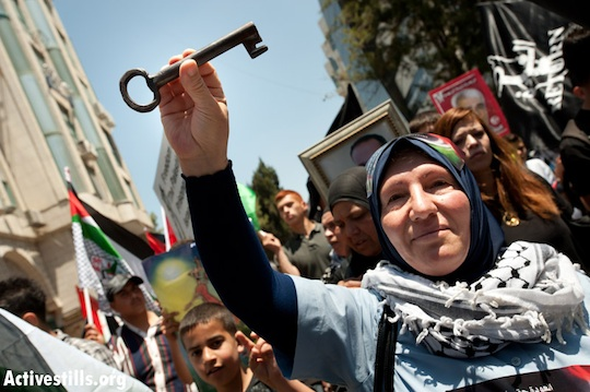 A Palestinian woman carries a key, a symbol of the Nakba and the right of return, May 15, 2012, Ramallah. (Ryan Rodrick Beiler/Activestills.org)