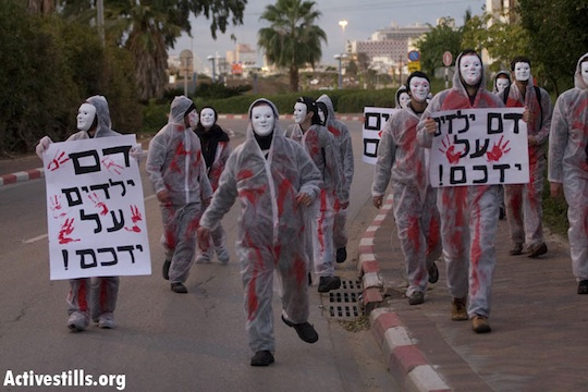 """Protesters in white suits covered in fake blood arrive at Sde Dov Air Force Base in north Tel Aviv to protest Operation Cast Lead, January 2, 2013. The signs read: """"You have children's blood on your hands."""" (Photo: Activestills.org)"""